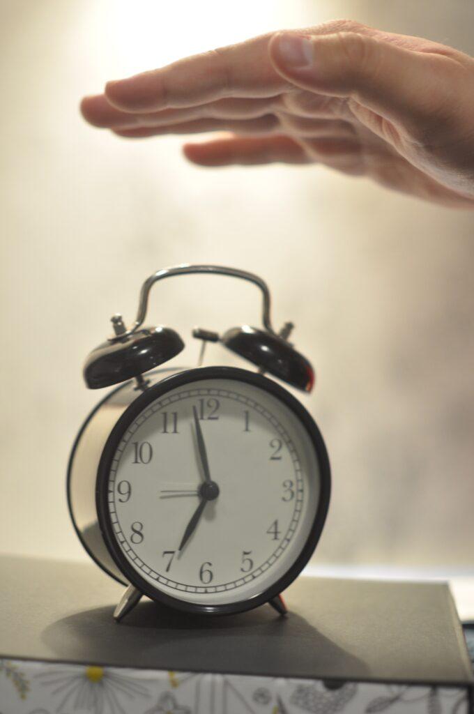Someone hitting snooze on their alarm clock